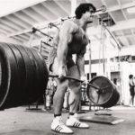 спортсмен поднимает штангу